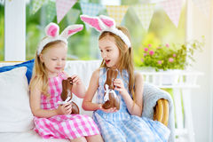 Two cute little sisters wearing bunny ears eating chocolate Easter rabbits. Kids playing egg hunt on Easter. Royalty Free Stock Images