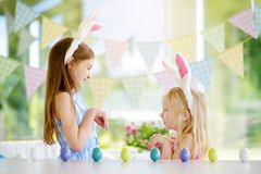 Two cute little sisters wearing bunny ears playing egg hunt on Easter Stock Image