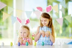 Two cute little sisters wearing bunny ears playing egg hunt on Easter. Adorable children celebrate Easter at home Royalty Free Stock Image