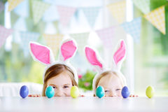 Two cute little sisters wearing bunny ears playing egg hunt on Easter. Adorable children celebrate Easter at home Royalty Free Stock Photography