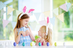 Two cute little sisters wearing bunny ears playing egg hunt on Easter Royalty Free Stock Images
