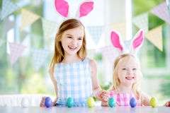 Two cute little sisters wearing bunny ears playing egg hunt on Easter Stock Photos