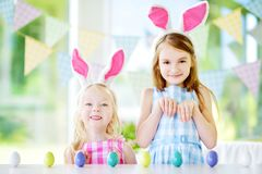 Two cute little sisters wearing bunny ears playing egg hunt on Easter Stock Images