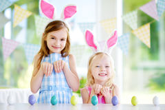 Two cute little sisters wearing bunny ears playing egg hunt on Easter Royalty Free Stock Photo