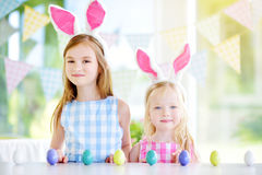 Two cute little sisters wearing bunny ears playing egg hunt on Easter Royalty Free Stock Photos