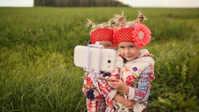 Two cute little twin sisters photograph themselves on a green meadow, using a phone and a stick for selfie. stock footage