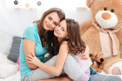 Two cute lovely sisters sitting and hugging Royalty Free Stock Photography