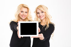 Two cute lovely sisters twins showing blank tablet computer screen Royalty Free Stock Images
