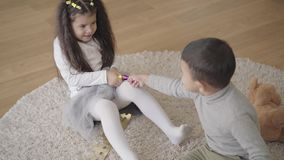 Two cute Middle Eastern children fighting for the toy. Brother trying to take away the party whistle from his sister stock video