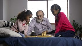 Two cute mixed race sisters playing chess at home stock video footage