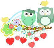 Two cute owls and bird on the flower tree branch Royalty Free Stock Images