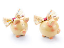 Two cute piggy banks with a banknote bow Royalty Free Stock Photo