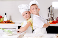 Two cute proud young chefs. With a little boy and girl standing back to back in the kitchen in their white uniforms and toques with folded arms smiling at the Royalty Free Stock Photography