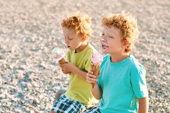 Two cute red curly boys brothers are extremely happy while eating ice cream on the summer beach stock photo