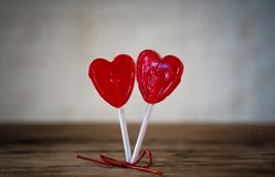Two red heart shaped lollipops as metaphor of love, togetherness and Valentines day concept royalty free stock photography