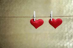 Two cute red hearts hanging from a string by white clothes peg. Valentine`s Day or romantic occasion with copy space. Horizontal photo of two cute red hearts stock photography