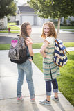 Two cute school girls heading off to school Stock Photo