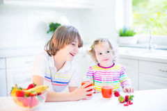 Two cute siblings having fruit for breakfast drinking juice Royalty Free Stock Photo