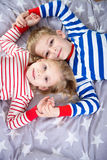 Two cute siblings lying on bed. Fokus frome above Stock Photos