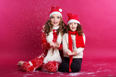 Two cute sisters are blowing fake snow in studio Royalty Free Stock Photo