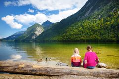 Two cute sisters enjoying the view of deep green waters of Konigssee, known as Germany`s deepest and cleanest lake, located in th. E extreme southeast royalty free stock images