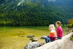 Two cute sisters enjoying the view of deep green waters of Konigssee, known as Germany`s deepest and cleanest lake, located in th Stock Images