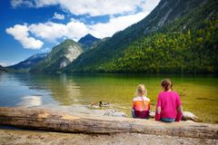Two cute sisters enjoying the view of deep green waters of Konigssee, known as Germany`s deepest and cleanest lake, located in th Royalty Free Stock Photos