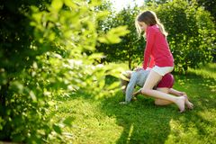 Two cute sisters fooling around together on the grass on a sunny summer day. Children being silly and having fun stock images