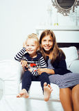 Two cute sisters at home interior playing, little happy smiling Stock Image