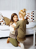 Two cute sisters at home playing, little girl in house interior, lifestyle people concept Royalty Free Stock Image
