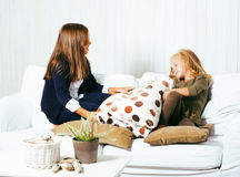 Two cute sisters at home playing, little girl in house interior Stock Photos