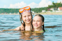 Two cute sisters hugging in the sea water stock images