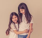 Two cute sisters playing together having fun posing and modeling royalty free stock photography