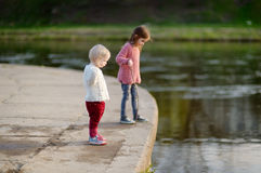 Two cute sisters by a river royalty free stock images