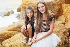 Two cute sisters sitting on the beach Stock Images