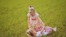 Two cute sisters twins frolicking on a green meadow in summer day. Falling on the grass, laughing and hugging. Two cute sisters twins frolicking on a green stock footage