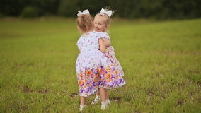Two cute sisters twins frolicking on a green meadow in summer day. Holding hands smile at each other. Two cute sisters twins frolicking on a green meadow in stock footage