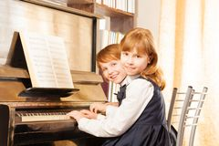 Two cute small girls in uniforms playing piano Stock Photography