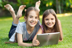 Two cute smiling girls lying on grass at park with digital table Royalty Free Stock Photos