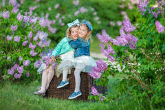Two cute smiling girls sisters lovely together on a lilac field bush all wearing stylish dresses and jeans coats. Stock Photography
