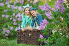 Two cute smiling girls sisters lovely together on a lilac field bush all wearing stylish dresses and jeans coats. Royalty Free Stock Image