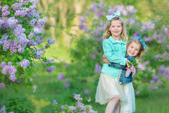 Two cute smiling girls sisters lovely together on a lilac field bush all wearing stylish dresses and jeans coats. Stock Images