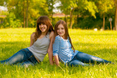Two cute smiling teenage girls sitting on the gras Stock Images