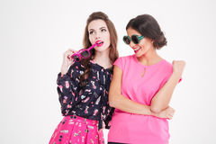 Two cute smiling young women in sunglasses standing and thinking Royalty Free Stock Photography
