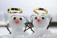 Two cute snowman angles with golden halos. And reading glasses and their wooden twig arms in the air. Snow fall on the ground at winter Stock Photo