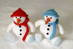 Two cute snowmen sitting in the snow Royalty Free Stock Photo
