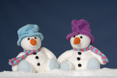 Two cute snowmen sitting in the snow Stock Photo