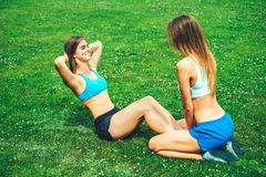 Two cute sporty girls workout together outdoor stock photography