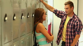 Two cute students flirting in the hallway beside lockers stock footage