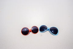 Two cute sunglasses on the beach Stock Photos